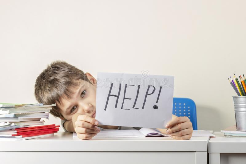 Sad tired frustrated boy sitting at the table with many books and holding paper with word Help. Learning difficulties royalty free stock photos