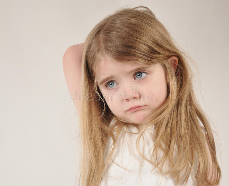 Sad and Tired Little Child. A little child looks sad and frustrated. The girl has her hand over her head for a parenting or tired concept royalty free stock images