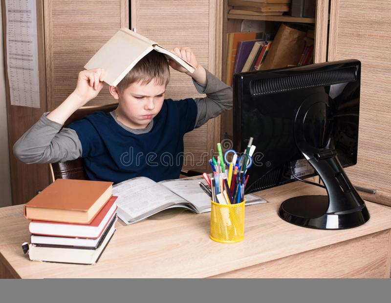 Sad and tired pre teen schoolboy sitting in stress working doing. Homework in his room stock photography
