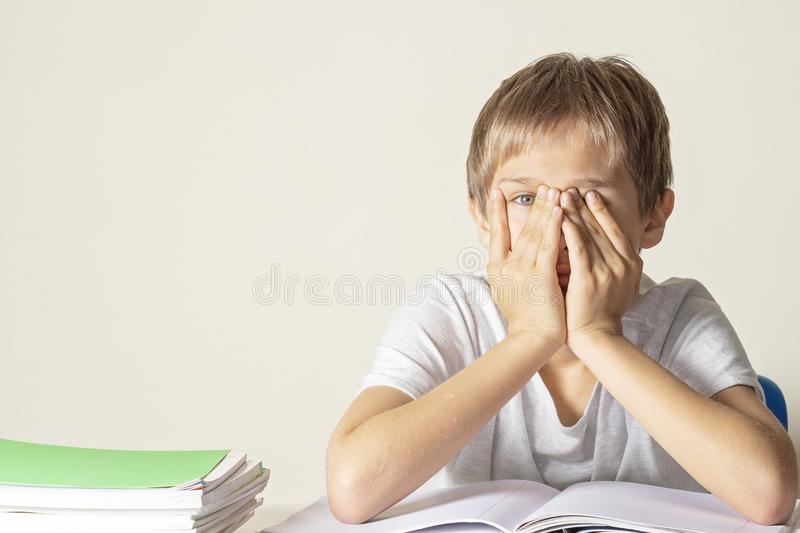 Sad tired upset schoolboy covering face with his hands sitting near table with pile of school books and notebooks stock photo