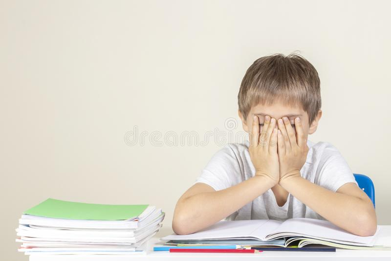 Sad tired upset schoolboy covering face with his hands sitting near table with pile of school books and notebooks royalty free stock photo