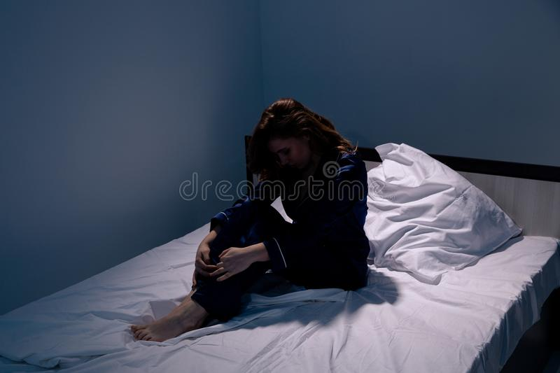 Sad and tired woman in the bed feeling sick. Insomnia and headache concept. royalty free stock images