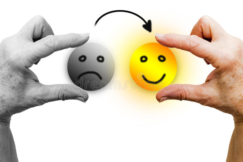 From sad to happy. The left hand of a woman in black and white holds a sad icon face. The right hand, in color, holds a happy smiling icon face, shining like the stock photography