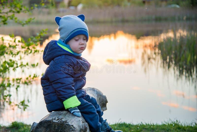 Sad toddler boy alone. Sitting on a bench royalty free stock image