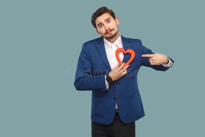 Sad unhappy broken heart man in blue jacket and white shirt, sta. Nding and holding red heart shape and looking at camera and pointing finger. Indoor, studio stock photo