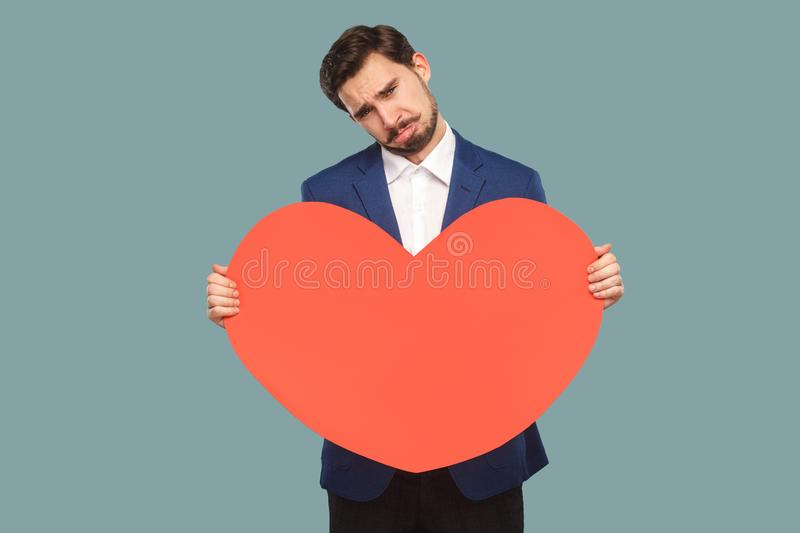 Sad unhappy businessman in blue jacket and white shirt standing. And holding red big heart shape and looking at camera with cry and broken heart. Indoor, studio royalty free stock photo