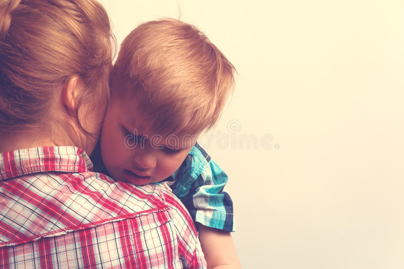 Sad unhappy child hugging his mother stock images