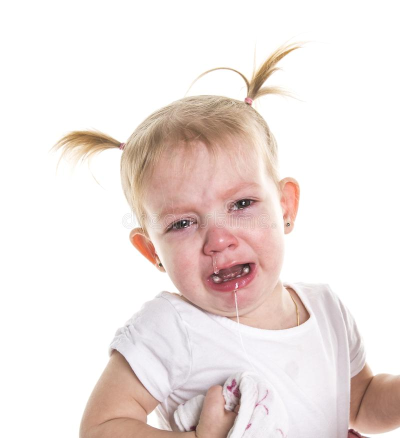 Sad unhappy crying cute little young toddler girl wiping tears, isolated. stock photos