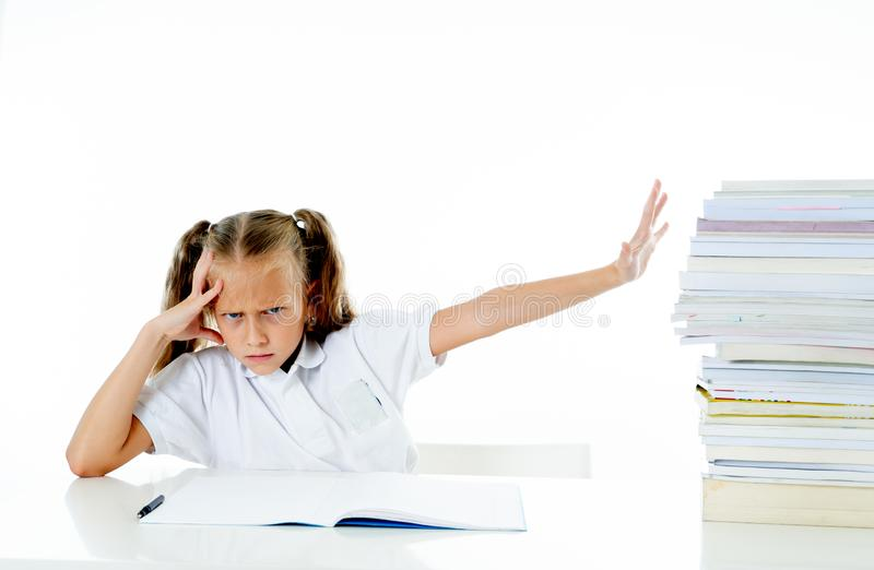 Sad unhappy cute little girl overwhelm with homework and studies. Sad and tired cute schoolgirl with blond hair sitting in stress doing homework overwhelm with stock photos