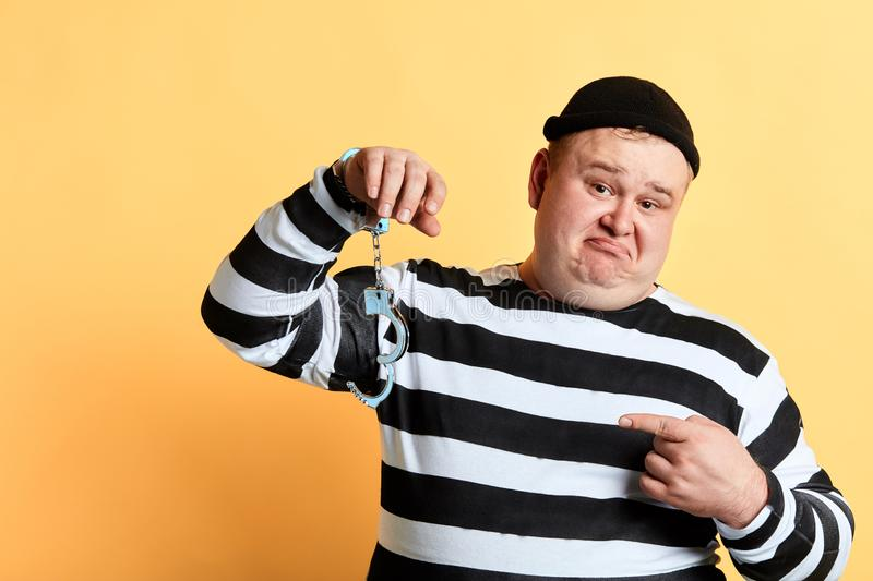 Sad unhappy fat man pointing to unlocked handcuffs hanging on his hand royalty free stock photos