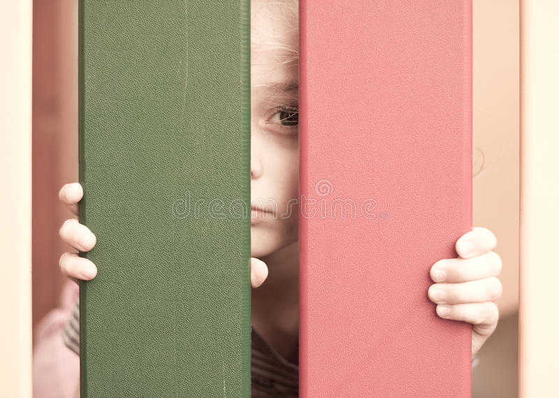 Sad unhappy five years old child girl. Sad unhappy five years old blond caucasian child girl looking through the fence royalty free stock images