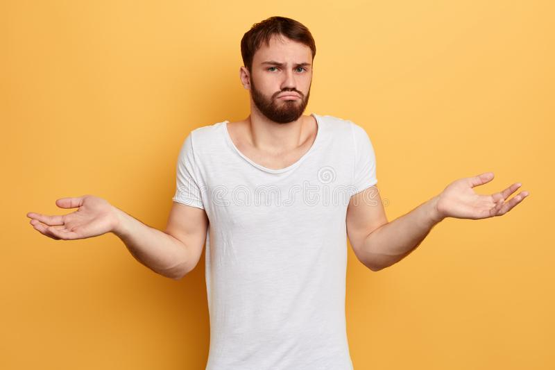 Sad unhappy guy srugging shoulders and looking at the camera stock photography