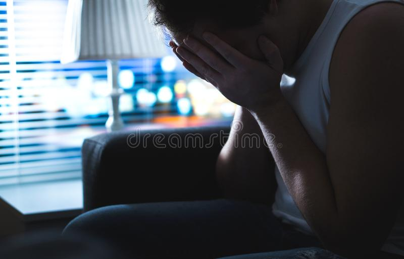 Sad and unhappy man covering face with hands in dark by window. Burnout, overwork or bankruptcy. Heartbroken person missing at night. Ashamed guy having regret stock photos