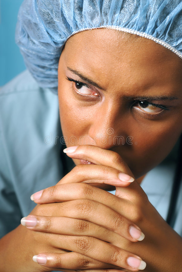 Sad and unhappy nurse. Portrait of a young nurse looking unhappy and tired royalty free stock photo