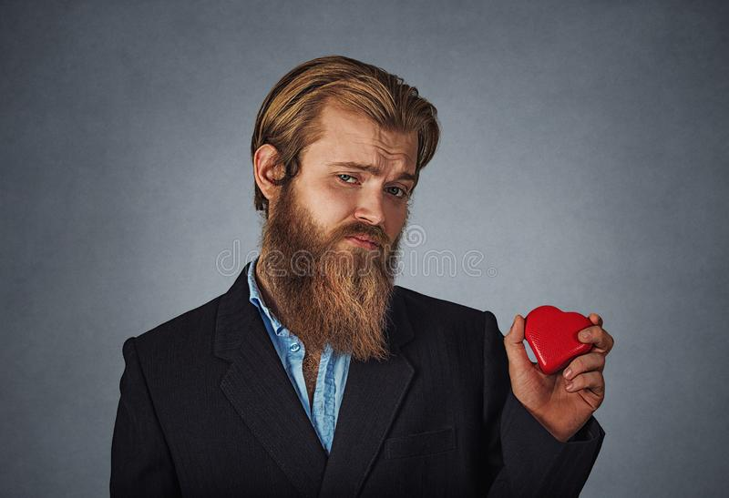 Upset man standing and holding red big heart shape. Sad unhappy skeptical hipster businessman in black jacket, blue shirt standing and holding red big heart royalty free stock photos