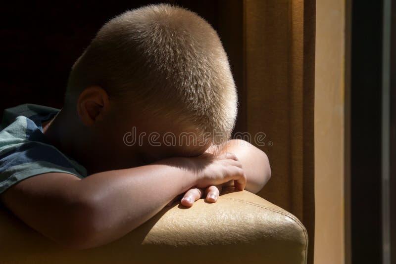 Sad upset child. Sad upset waiting boring depressed child (boy) near a window stock photo