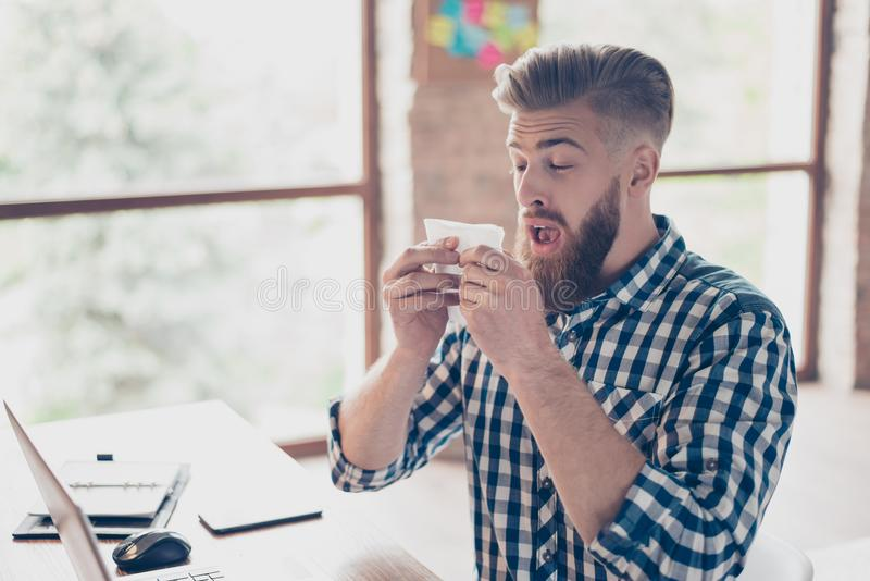 Sad upset ill handsome attractive coughing with high temperature. Closed eyes manager business businessman freelancer feeling discomfort using paper tissue stock image