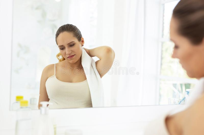Sad upset woman suffering from discomfort. Bad mood. Gloomy unhappy woman using towel and looking down stock image