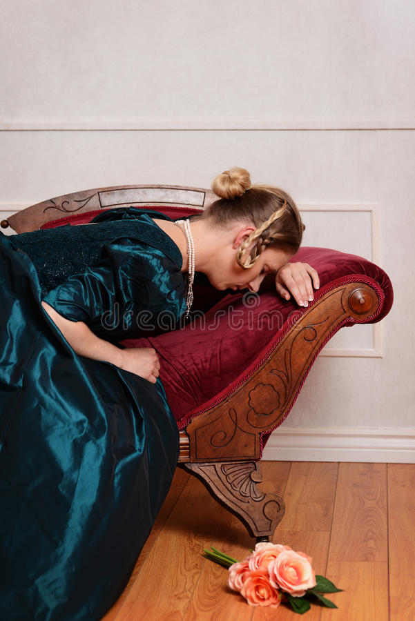 Sad victorian woman on fainting couch stock photography