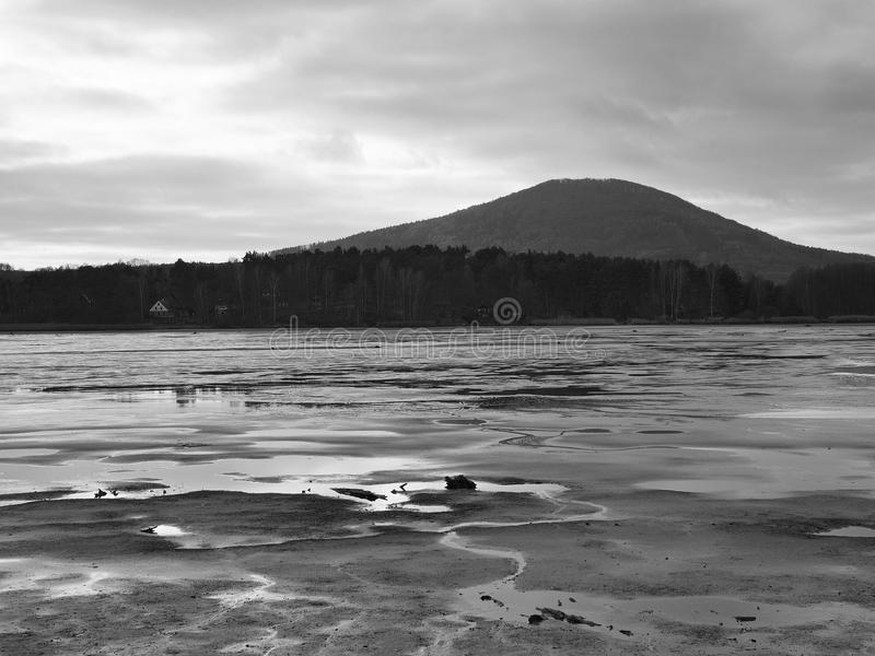 Sad view over empty pond to hill and forest on oposite bank. Autumn melancholic atmosphere. Black and white photo stock images