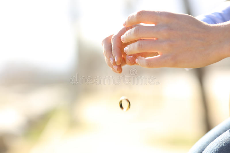 Sad wife hands dropping her wedding ring. Marriage problems concept stock images