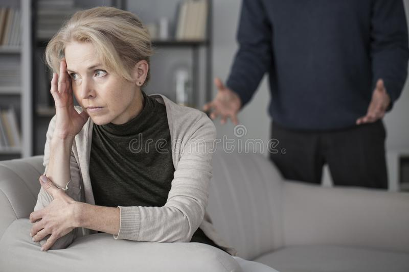Sad wife looking ahead. Sitting on a sofa in a room with her angry husband behind her royalty free stock images