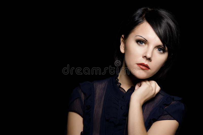 Sad woman. Studio portrait of young caucasian sad woman, over black royalty free stock photography