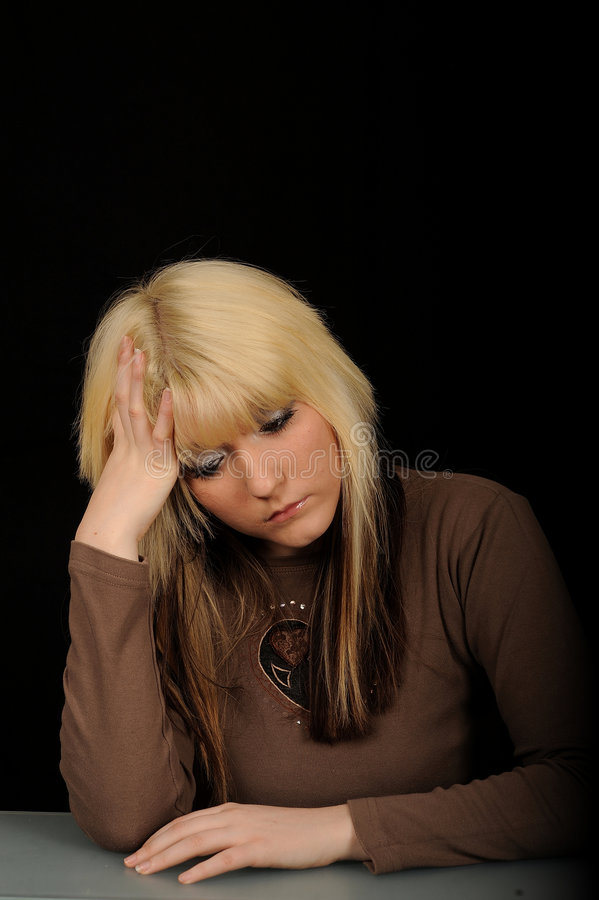 Sad woman. Half body portrait of young blond woman with sad expression holding head with hand, black background royalty free stock image