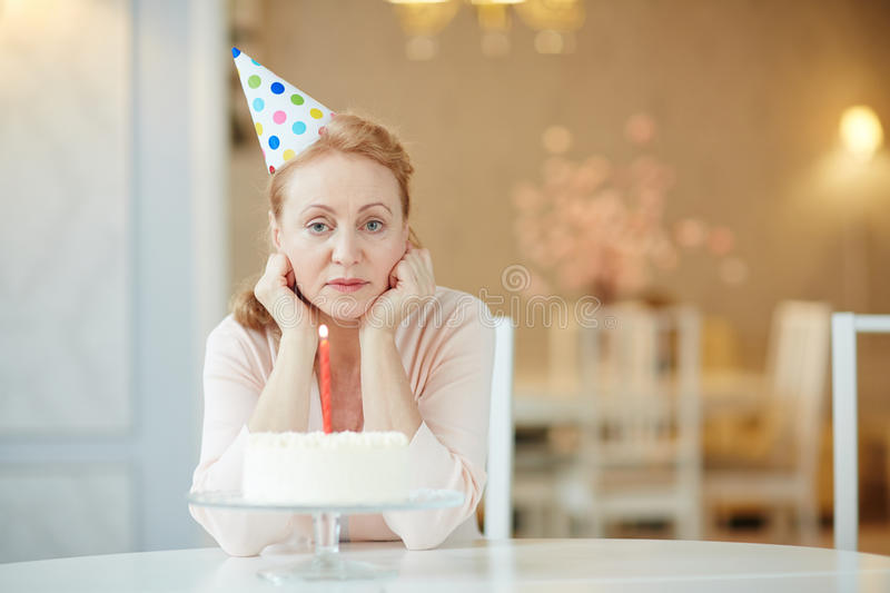 Sad Woman Alone on Birthday. Portrait of sad lonely mature woman sitting alone at birthday table with cake , wearing party hat and looking at camera stock image