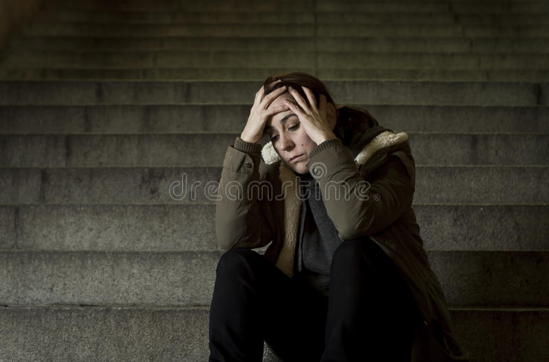 Sad woman alone on street subway staircase suffering depression looking looking sick and helpless stock image