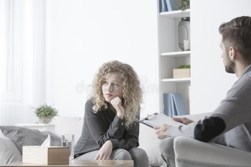 Sad woman with anxiety problem. Sad women with anxiety problem talking to a psychotherapist royalty free stock images