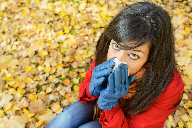 Sad woman in autumn flu and cold outside. Sad woman with flu blowing her nose with a tissue on a cold day. Caucasian model lying sitting outside on autumn golden stock image
