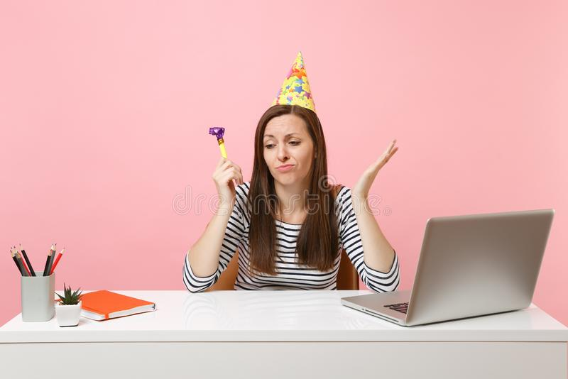 Sad woman in birthday hat with playing pipe feeling unhappy because nobody came to celebrate sit work at white desk with. Pc laptop isolated on pink background stock image