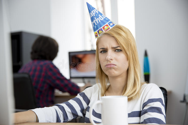 Sad woman with birthday hat sitting at the table. In office and looking at camera royalty free stock images