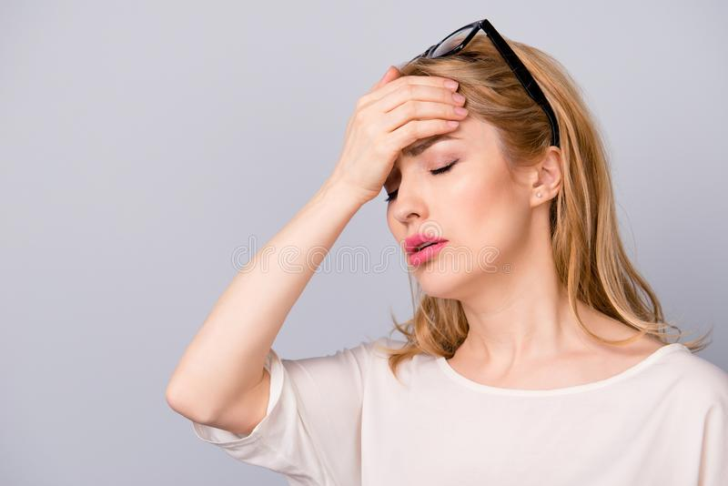 Sad woman with blonde hair touching her forehead because of having terrible headache stock photo