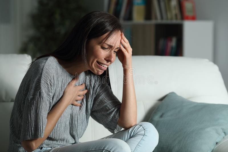Sad woman with broken heart complaining at home royalty free stock photography