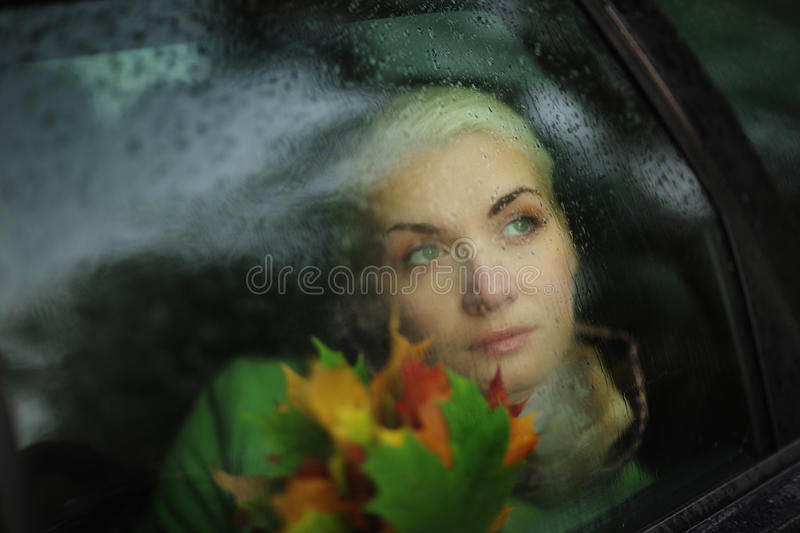 Sad woman in car. Behind wet glass stock photography