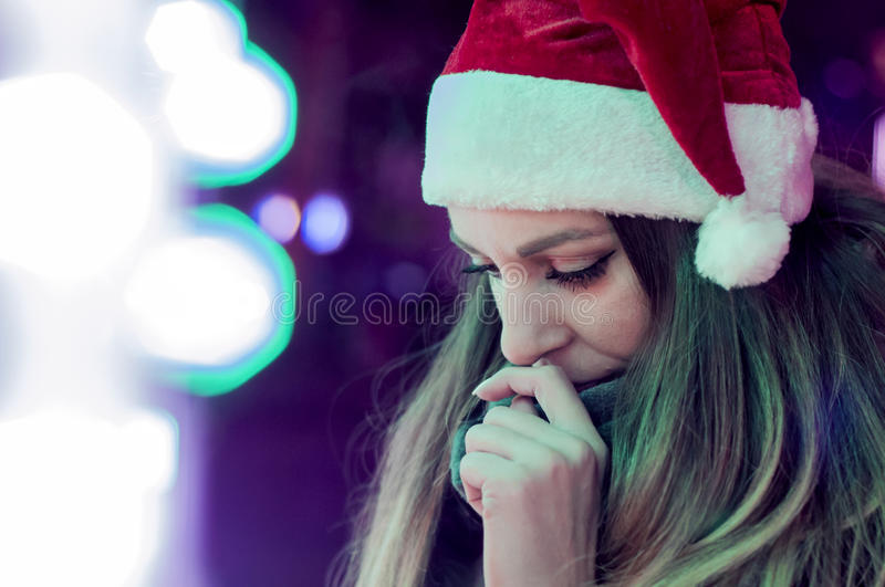 Sad woman by the christmas tree contemplating. Lonely Christmas stock photography