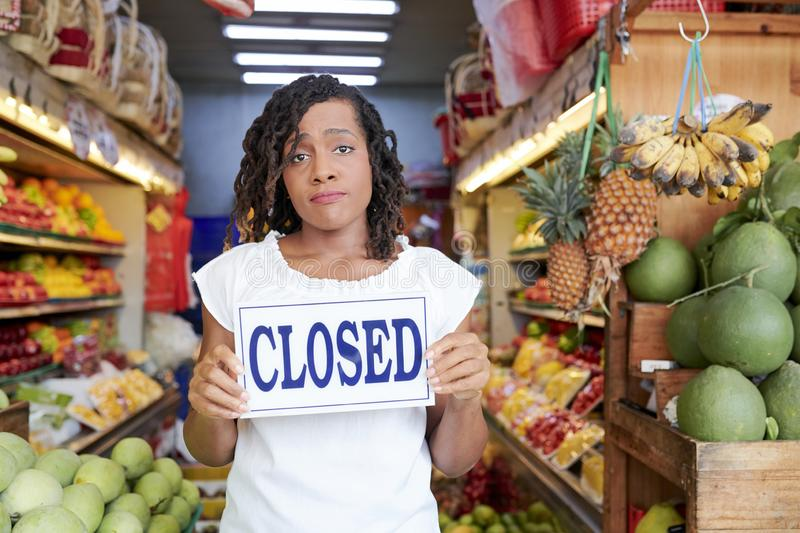 Sad woman closing store. Sad Black young woman closing her grocery store with no customers inside stock image