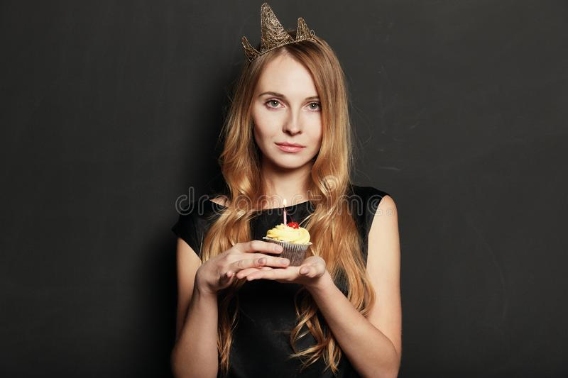 Sad woman, with a crown, holding a birthday cupcake stock photos