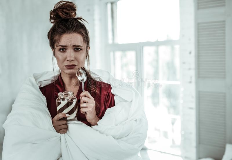 Sad woman eating the chocolate pasta to reduce the stress royalty free stock photos