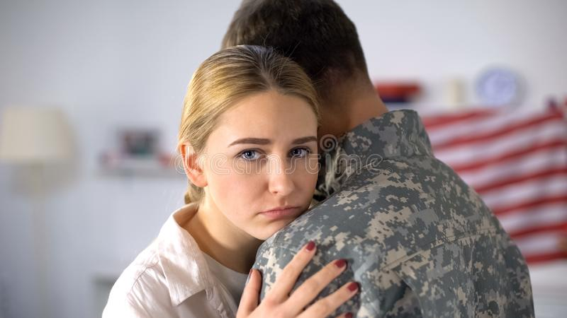 Sad woman embracing soldier leaving home, farewell before military service stock photography
