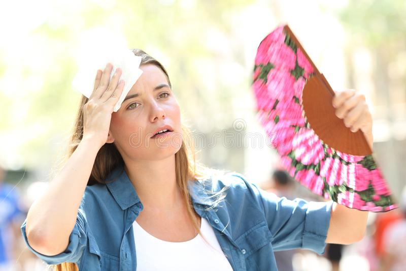 Sad woman fanning and sweating suffering a heat stroke. On summer in the street royalty free stock photos