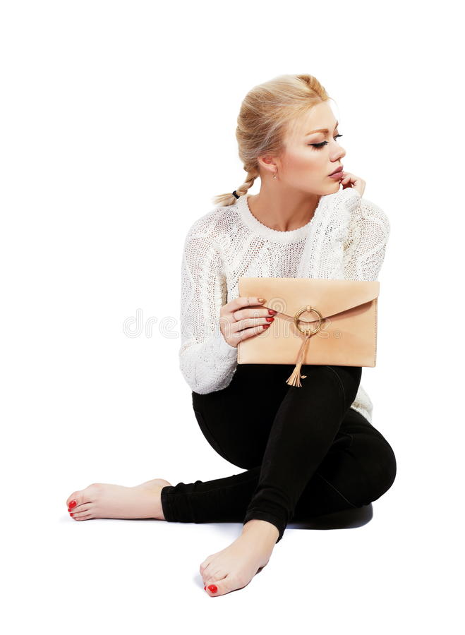Sad woman. Full length portrait of beautiful young woman siiting and holding purse in the hand isolated on white in photostudio royalty free stock images