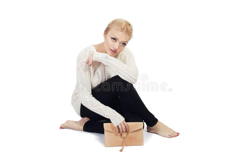 Sad woman. Full length portrait of beautiful young woman siiting and holding purse in the hand isolated on white in photostudio royalty free stock photo