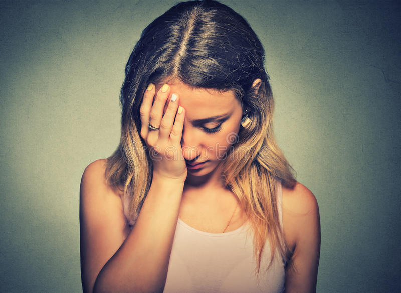 Sad woman on gray wall background royalty free stock images