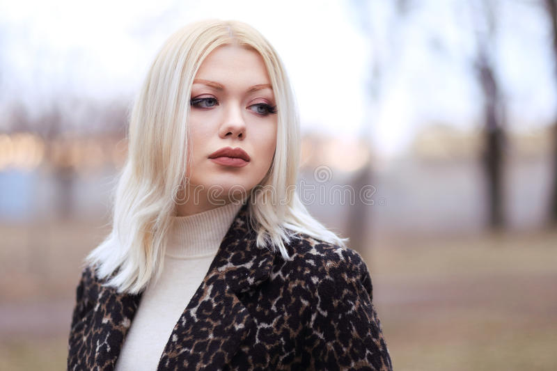 Sad woman. Half length portrait of young sad blond woman walking in the park in sunset stock photography