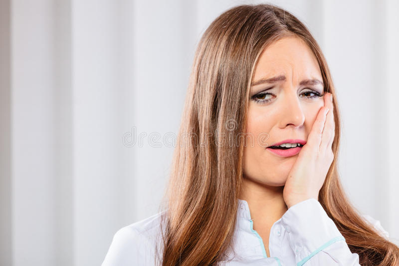 Sad woman with hand on cheek. Sadness and emotional distress. Stressful situation in work trouble and anxiety. Young woman in white shirt cry royalty free stock photo