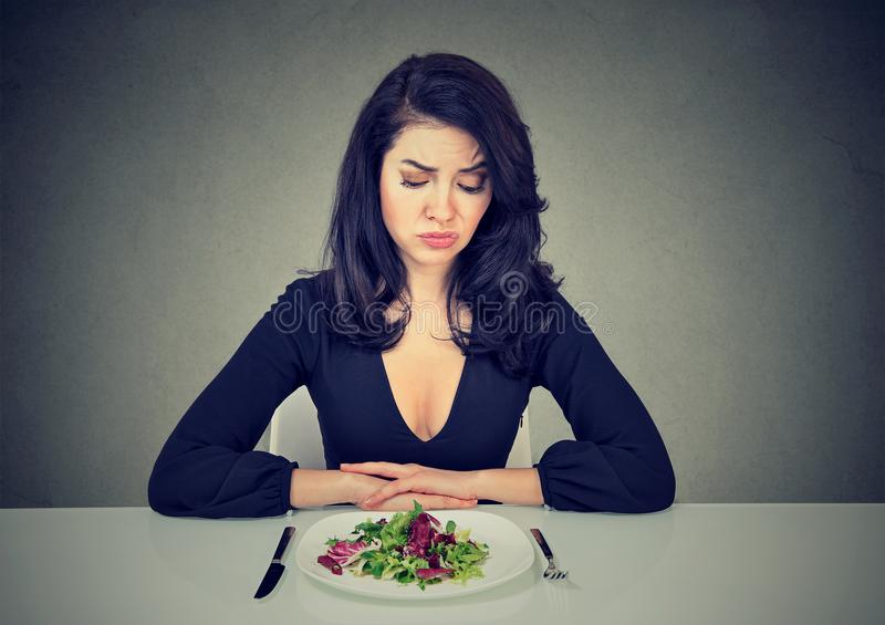 Sad woman having dissatisfying diet. Young woman looking at plate of salad with desperate expression having diet royalty free stock photo