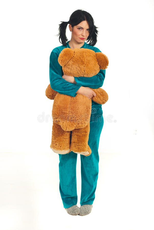 Sad woman holding big teddy bear. Full length of sad woman in pajamas holding big teddy bear isolated on white background stock images